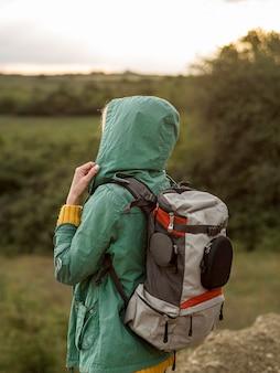 Vista lateral feminina com mochila ao pôr do sol