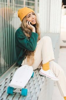 Vista lateral feminina com skate falando por telefone
