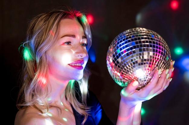 Vista lateral feminina na festa com o globo