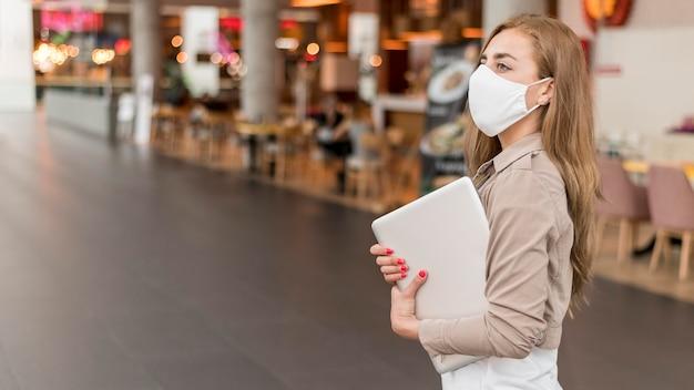 Vista lateral feminina no shopping com laptop usando máscara