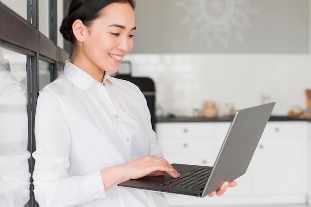 Vista lateral feminino trabalhando no laptop