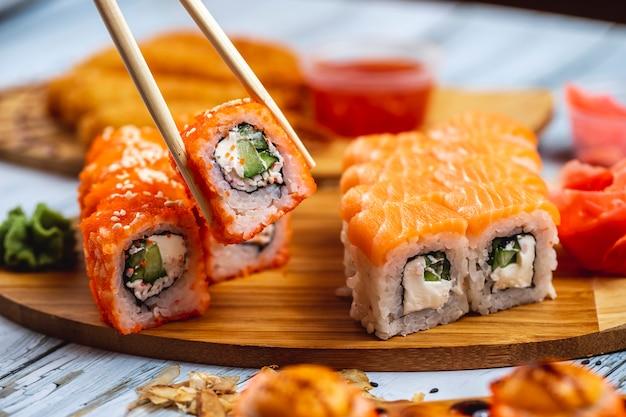 Vista lateral filadélfia e califórnia rola com carne de caranguejo creme de leite pepino tobiko caviar salmão creme de queijo molho de soja e gengibre em uma placa