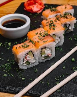 Vista lateral filadélfia roll salmão com carne de caranguejo abacate pepino endro gengibre e molho de soja em uma bandeja