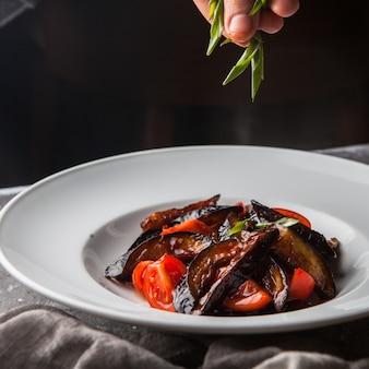 Vista lateral frita berinjela com tomate e cebolinha picada e mão humana em prato branco redondo