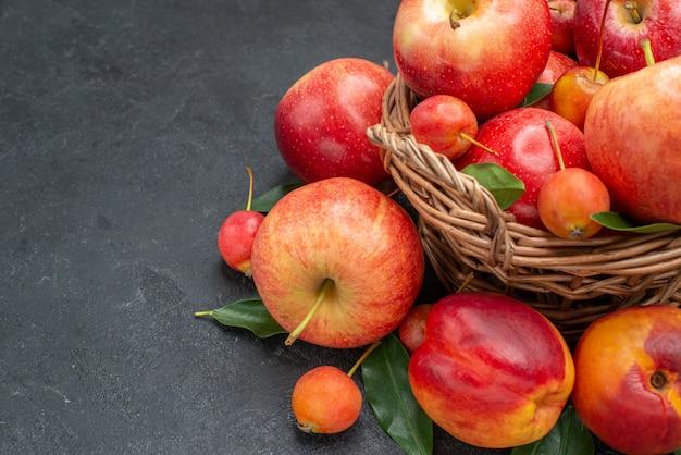 Vista lateral frutas a cesta de madeira com maçãs cerejas nectarina com folhas