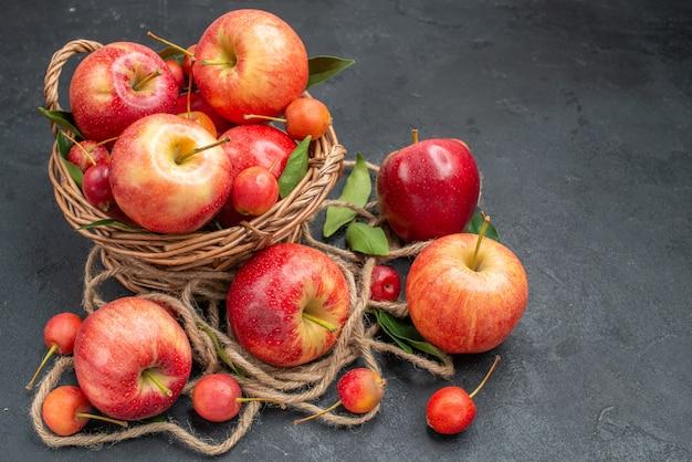 Vista lateral frutas maçãs cerejas na cesta ao lado das frutas e corda