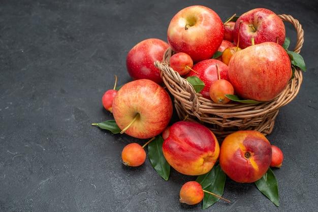 Vista lateral frutifica a cesta de madeira com frutas e bagas com folhas