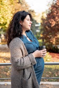 Vista lateral futura mãe com uma xícara de café