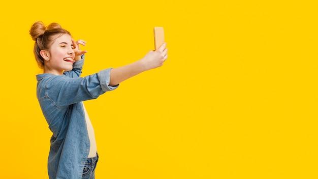 Vista lateral garota tomando selfie