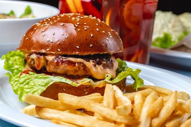 Vista lateral hambúrguer grelhado rissol de carne com molho de queijo derretido entre pães de hambúrguer e batatas fritas em cima da mesa
