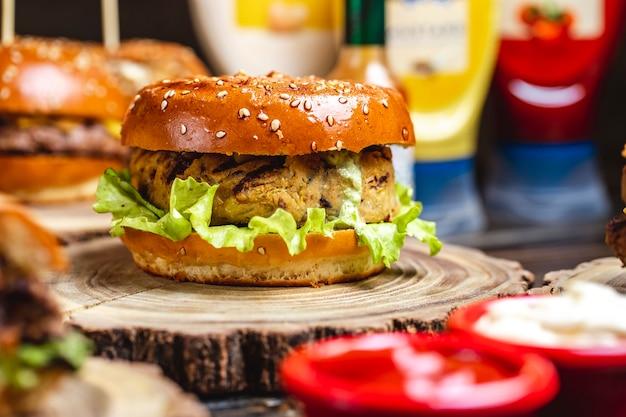 Vista lateral hambúrguer vegetariano vegetariana e folha de alface entre bolos de hambúrguer