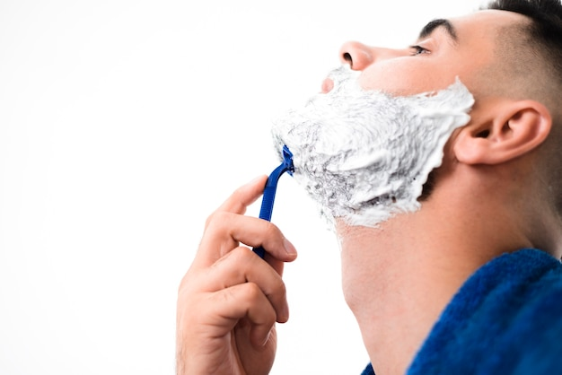Vista lateral homem bonito raspar sua barba close-up