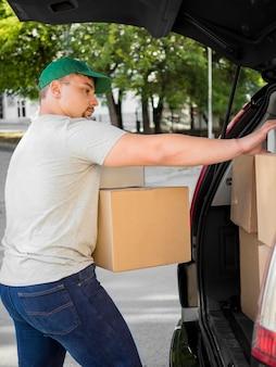 Vista lateral homem colocando caixas no porta-malas