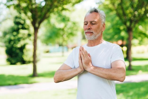Vista lateral homem com as mãos na posição meditando