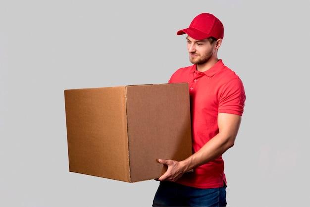 Vista lateral homem com caixa de embalagem