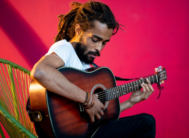 Vista lateral homem com dreads tocando guitarra