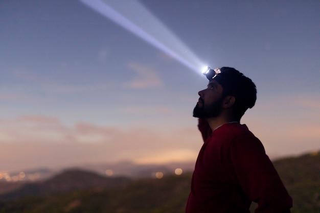 Vista lateral homem com lanterna de cabeça