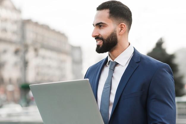Vista lateral homem com laptop