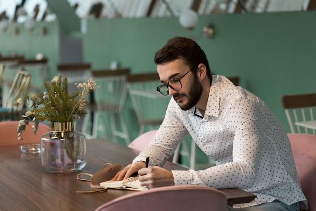 Vista lateral, homem de negócios, escrevendo na agenda