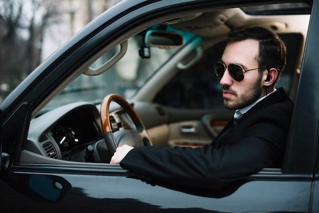 Vista lateral homem de segurança no carro