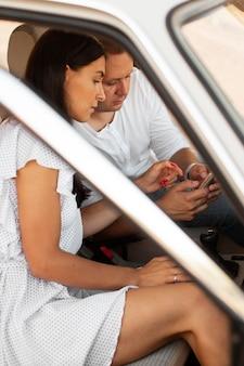 Vista lateral homem e mulher com telefone