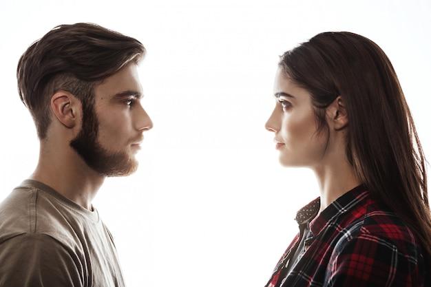 Vista lateral. homem e mulher de frente para o outro, olhos abertos.