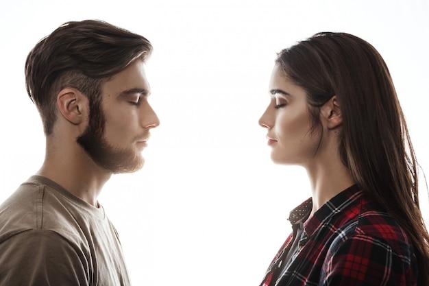 Vista lateral. homem e mulher de frente para o outro, olhos fechados.