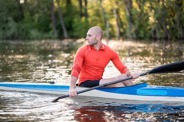 Vista lateral homem em canoa com remo