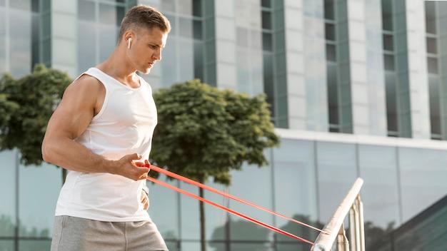 Vista lateral homem exercitando com uma faixa vermelha de alongamento