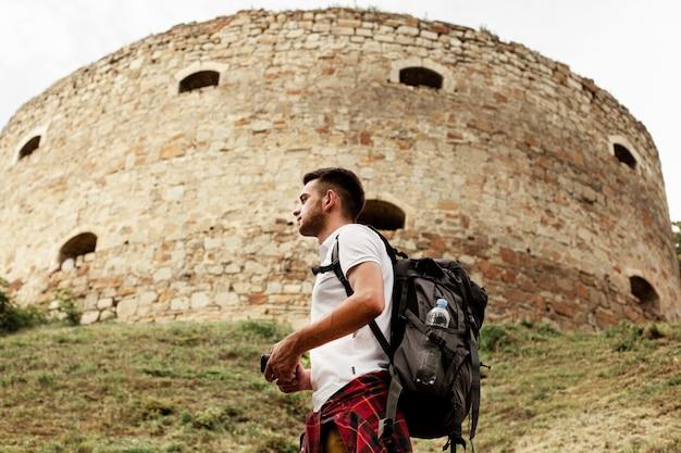 Vista lateral homem explorando ruínas