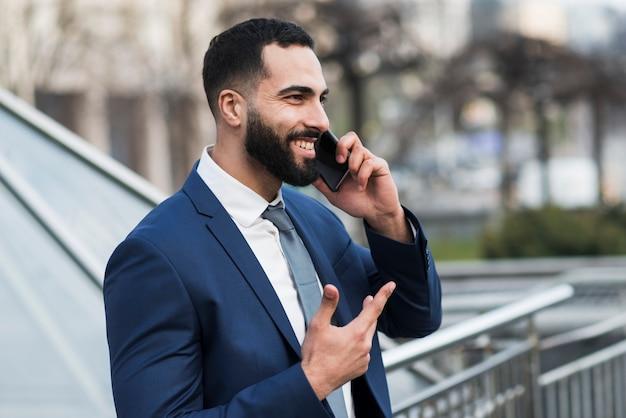 Vista lateral homem falando por telefone