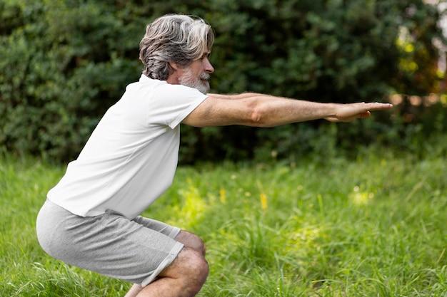 Vista lateral homem fazendo agachamentos ao ar livre