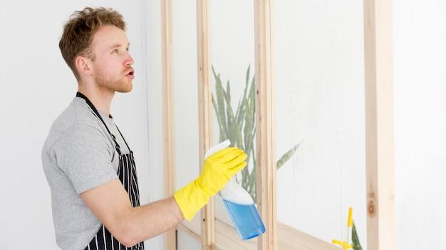 Vista lateral homem limpando janelas