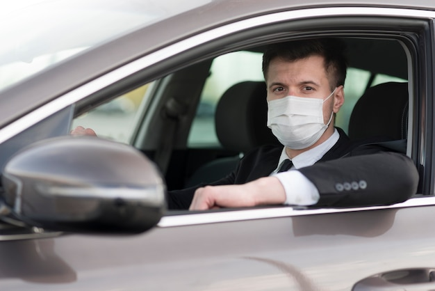 Vista lateral homem moderno no carro com máscara