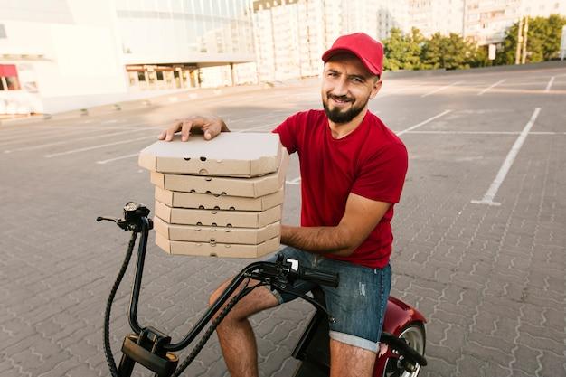 Vista lateral homem na moto segurando caixas de pizza