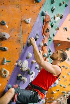 Vista lateral homem na parede de escalada