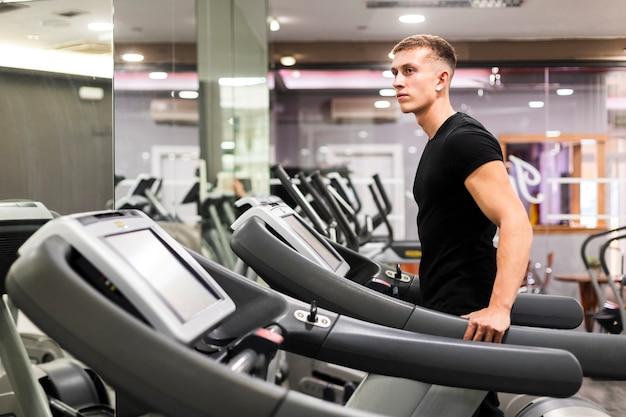 Vista lateral homem no ginásio em esteira