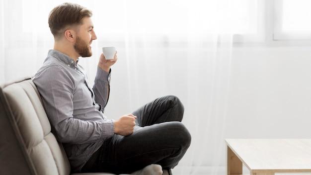 Vista lateral homem no sofá bebendo café