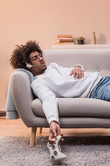 Vista lateral homem no sofá jogando jogos