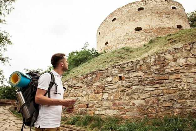 Vista lateral homem olhando ruínas do castelo