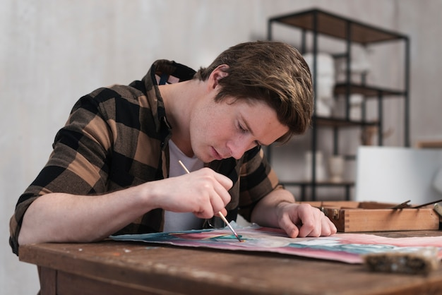 Vista lateral homem pintura em papel