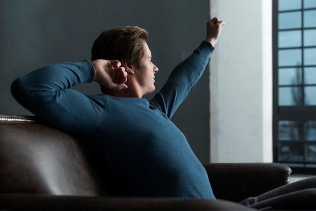 Vista lateral homem relaxante dentro de casa
