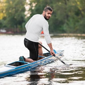 Vista lateral homem remando em canoa