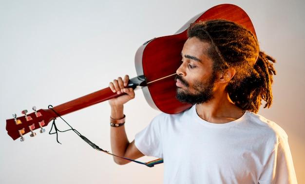 Vista lateral homem segurando seu violão no ombro