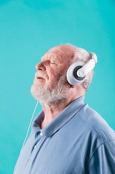 Vista lateral, homem sênior, apreciar música