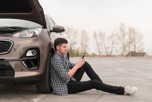 Vista lateral homem sentado ao lado de carro quebrado