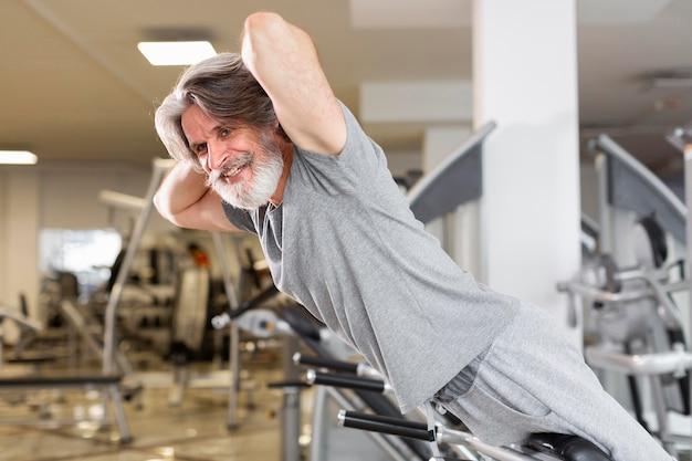 Vista lateral homem sorridente no ginásio