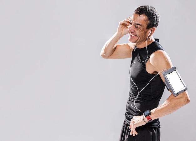 Vista lateral homem sporitve com fones de ouvido