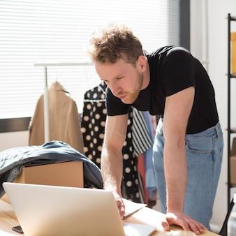 Vista lateral homem trabalhando no laptop