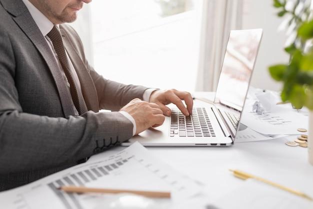 Vista lateral homem trabalhando no seu laptop